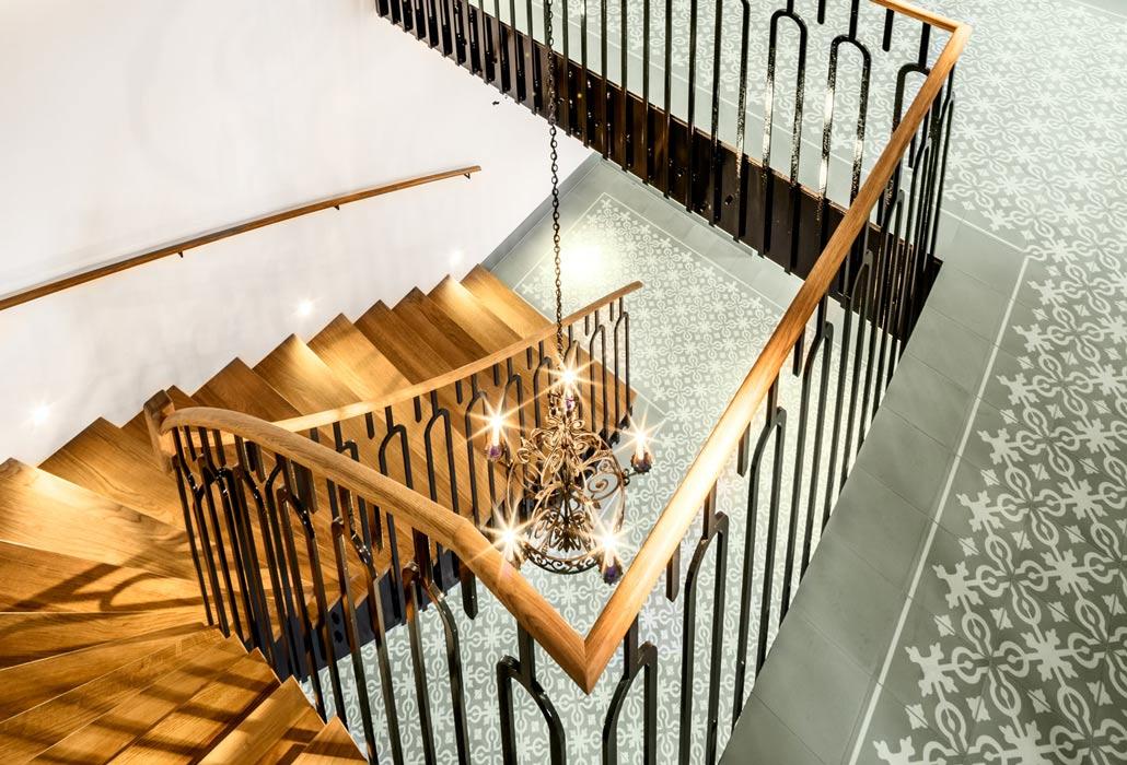 Traditionelles Stiegenhaus im Hotel mit Fliesenboden, Holztreppe und rustikalem Geländer
