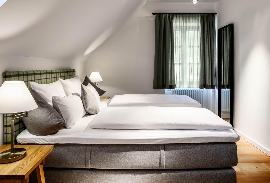 Hotelzimmer mit großem Doppelbett. Das Zimmer wurde mit grauen und grünen Farben gestaltet.