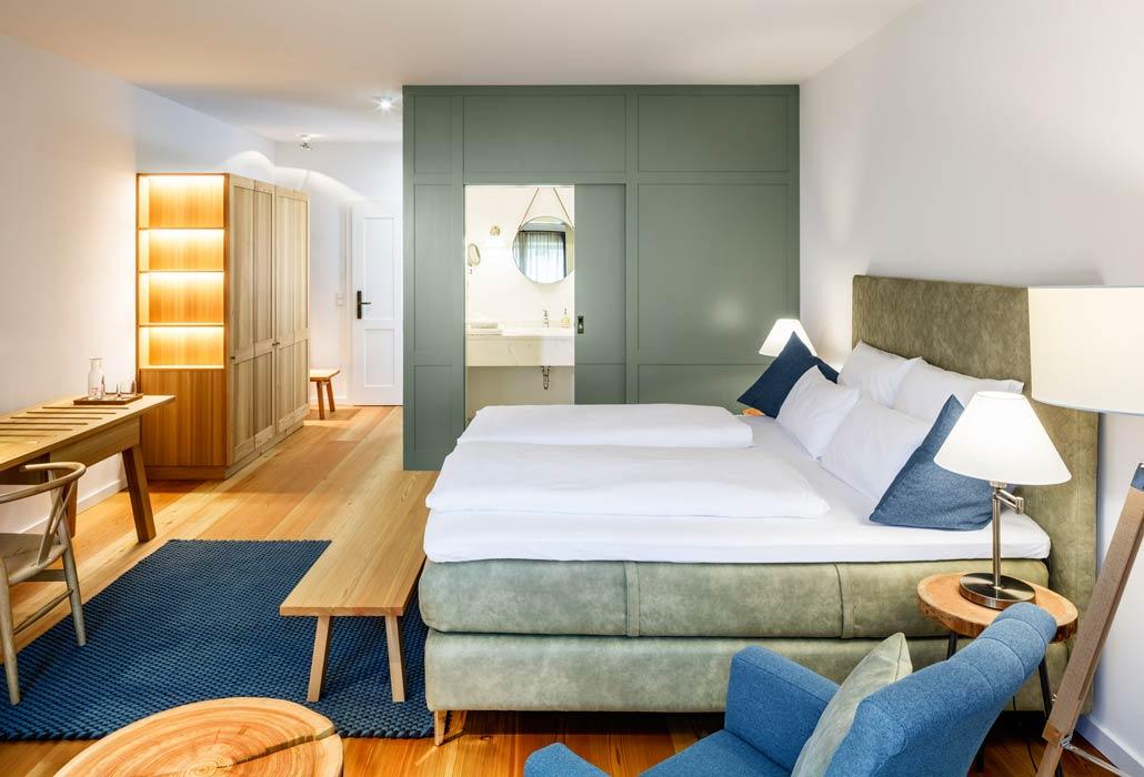 Helles Doppelzimmer mit vielen Holzelementen und einem gemütlichen Doppelbett.