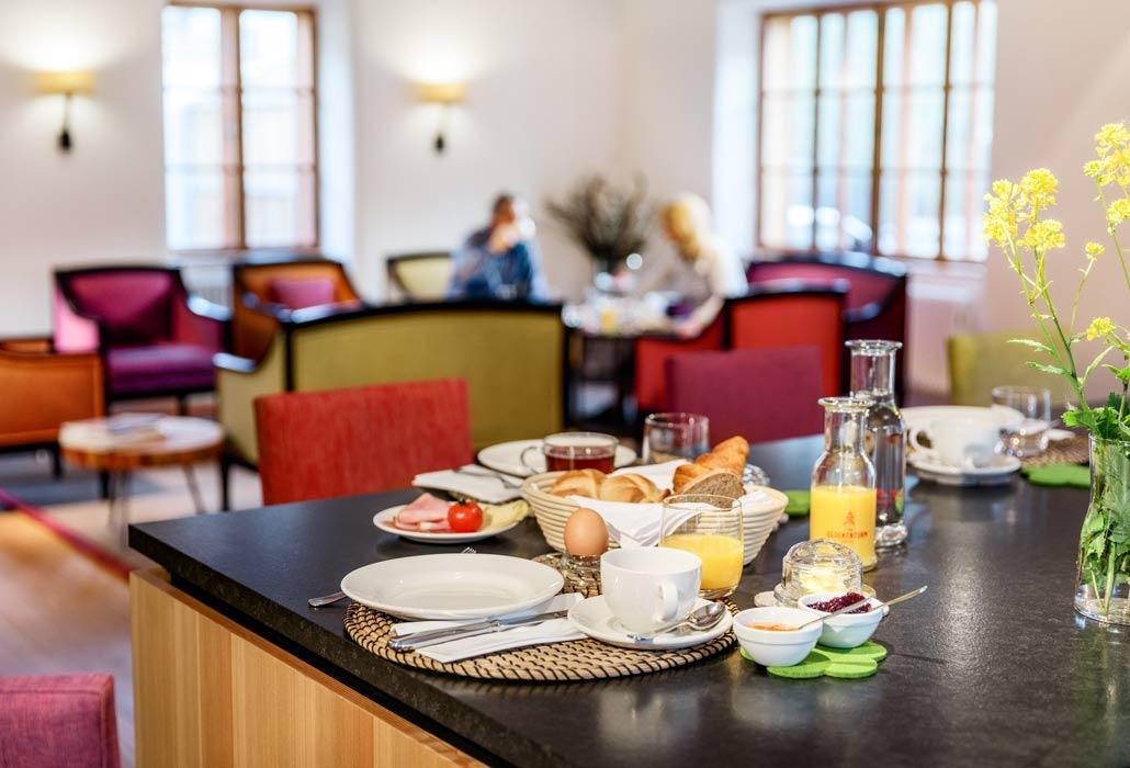 Aufgedecktes Frühstück im Foyer des Hotels. Im Hintergrund nehmen zwei Personen ebenfalls ihr Frühstück zu sich.
