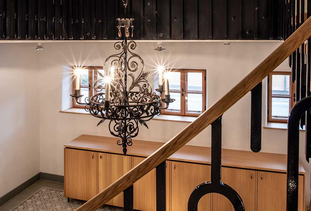 Stiegenhaus im Hotel zum Glockenturm mit rustikalem Geländer und Lampenschirm.